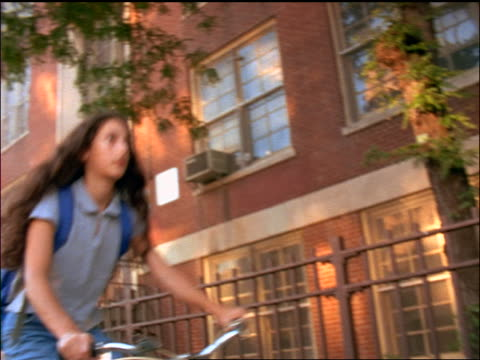 slow motion low angle pan schoolgirl wearing backpack riding bicycle on sidewalk past school - solo adolescenti femmine video stock e b–roll