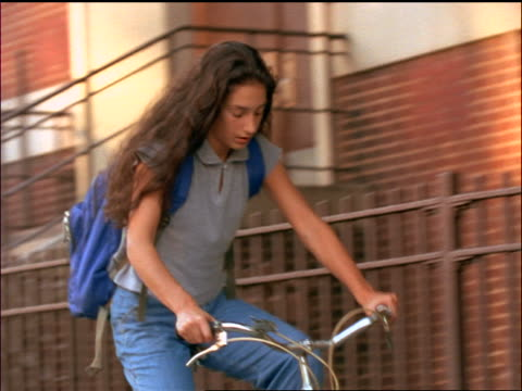 slow motion low angle pan schoolgirl wearing backpack riding bicycle on sidewalk - solo adolescenti femmine video stock e b–roll