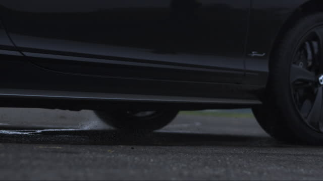 slow motion low angle shot of a car travelling along an airfield. - campo d'aviazione video stock e b–roll