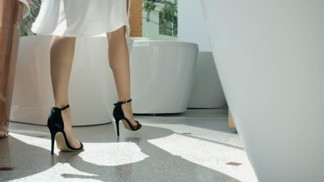 4kスローモーションローアングルショット、若い女性美しいドレス彼女はシャワーに歩いた - taking off点の映像素材/bロール