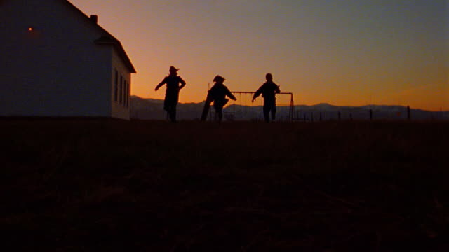 slow motion low angle silhouette of 3 children running toward camera / schoolhouse at twilight in background / Montana