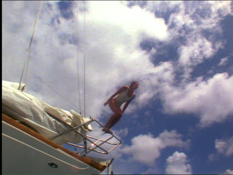 slow motion low angle tilt down woman with white swimsuit diving off sailboat railing into ocean water / Virgin Islands
