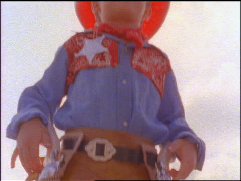 slow motion low angle tilt up boy wearing cowboy outfit with red cowboy hat