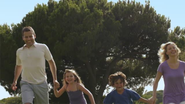 Slow motion low angle tilt up shot of family running in park/Marbella region, Spain