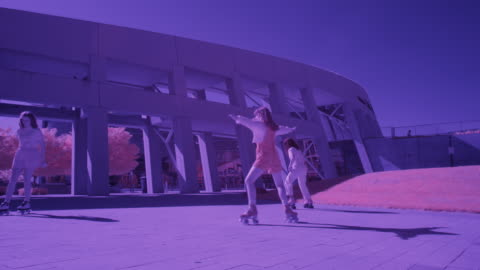 slow motion low angle toned image of girls roller skating in a circle / salt lake city, utah, united states - toned image stock videos & royalty-free footage