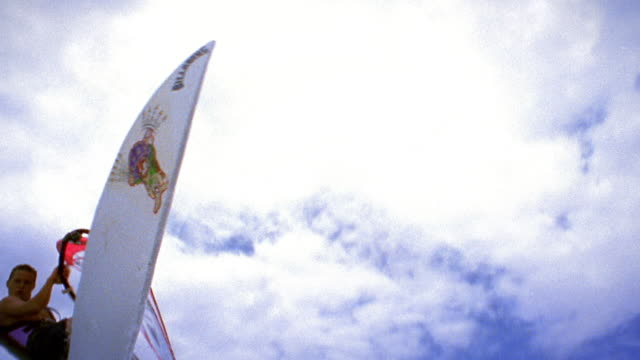 Slow motion low angle tracking shot man windsurfing jumps over and looks at camera, then lands / Maui, Hawaii