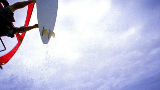 Slow motion low angle tracking shot man windsurfing jumps over camera, lands and wipes out / Maui, Hawaii