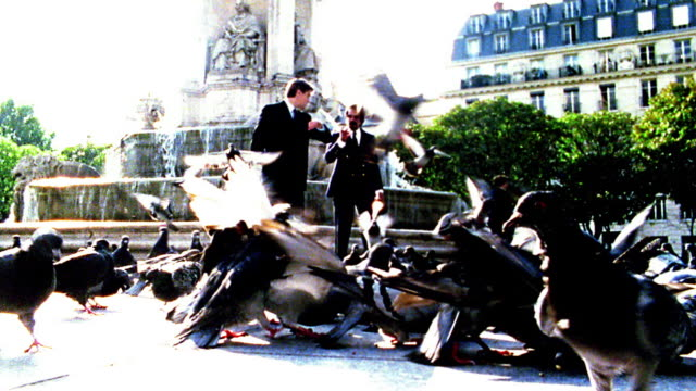 OVEREXPOSED slow motion low angle two businessman walk thru pigeons with fountain in background / Place Saint Sulpice