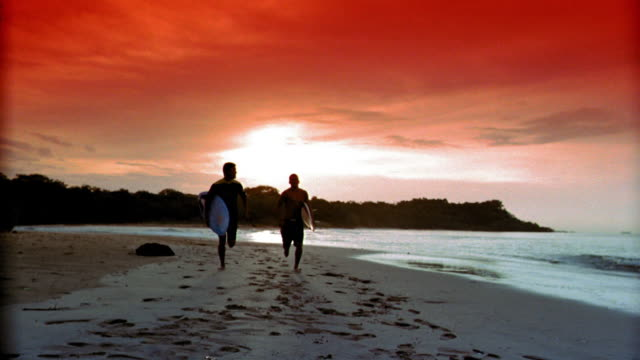 slow motion low angle two silhouetted men running toward + past camera on beach at sunset carrying surfboards