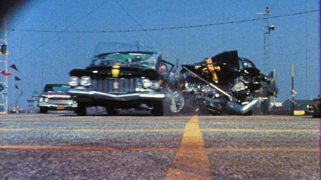 1968 slow motion low angle two test cars crashing + crash test dummy falling out - 試運転点の映像素材/bロール