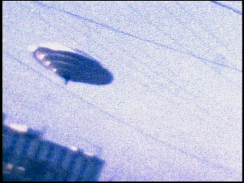 slow motion low angle ufo hovering over building - ufo点の映像素材/bロール