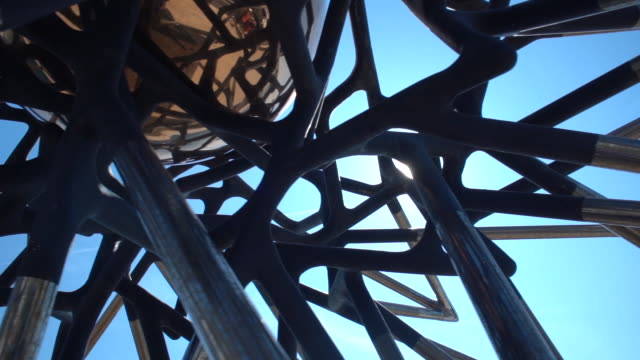 slow motion low angle view of a steel sculpture with the sun shinning through in monaco - stahl stock-videos und b-roll-filmmaterial