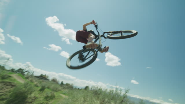 slow motion low angle view of boy jumping hill on bicycle at bike park / salt lake city, utah, united states - twisted stock videos & royalty-free footage