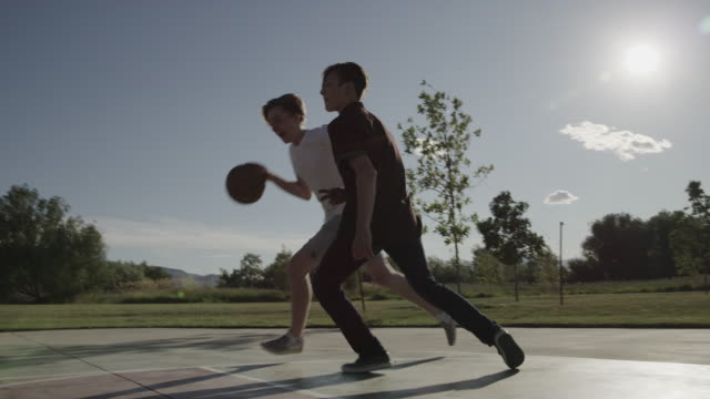 slow motion low angle view of boys playing basketball on court in park / lehi, utah, united states - lehi stock videos & royalty-free footage