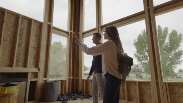 slow motion low angle view of couple pointing in interior of home under construction / pleasant grove, utah, united states - husband stock videos & royalty-free footage