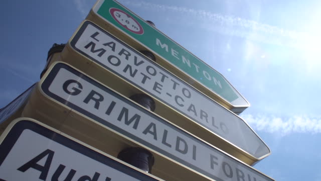 slow motion low angle view of directional road signs in monaco including menton, larvotto, grimaldi, auditorium rainier iii and avenue jf kennedy - monaco stock-videos und b-roll-filmmaterial