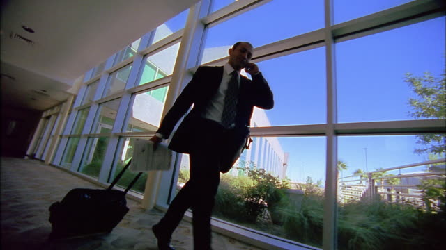 Slow motion low angle wide shot businessman on cell phone running and pulling wheeled suitcase past windows