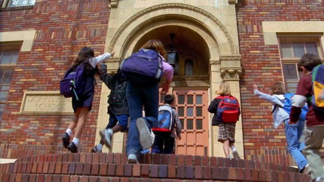 slow motion low angle wide shot children running up stairs to school with teacher opening and closing door - school building stock videos & royalty-free footage