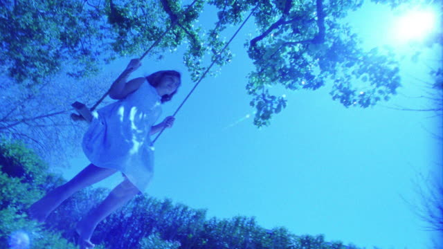 BLUE slow motion low angle wide shot girl swinging on tree swing / tree branches overhead