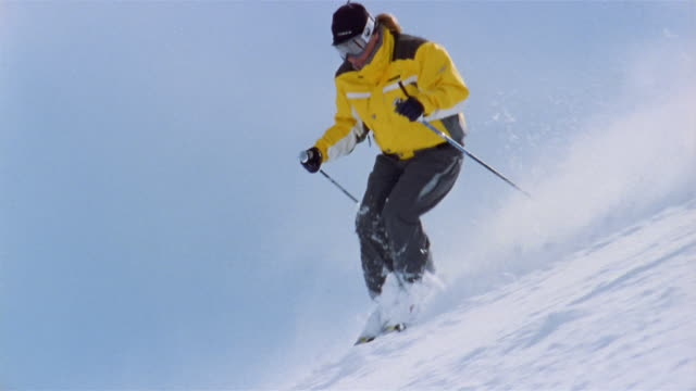 slow motion low angle wide shot man wearing yellow ski jacket and ski goggles skiing down slope / breckenridge, colorado - ski jacket stock videos & royalty-free footage