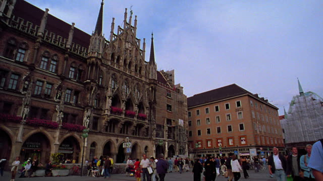vidéos et rushes de slow motion low angle wide shot pan neues rathaus + mariensaule / tilt down marienplatz with crowd / munich, germany - rathaus