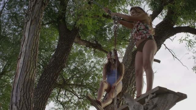 slow motion low angle wide shot of woman swinging into lake / mona, utah, united states - rope swing stock videos & royalty-free footage