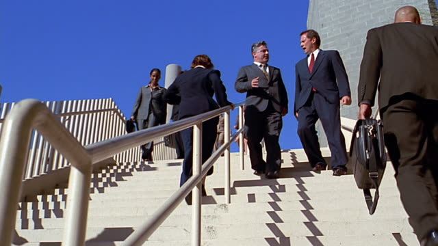 slow motion low angle wide shot pan business people walking up and down stairs / talking - aktentasche stock-videos und b-roll-filmmaterial