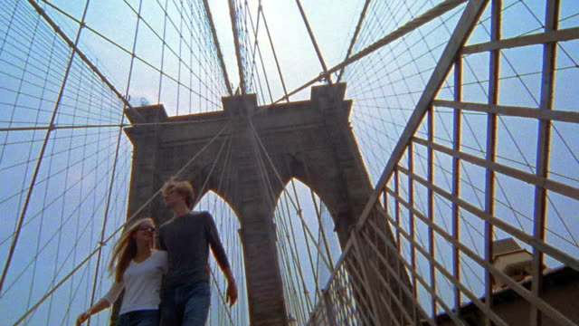 Slow motion low angle wide shot pan couple hugging and walking on Brooklyn Bridge pedestrian walkway