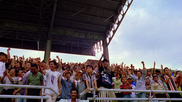 slow motion low angle wide shot pan crowd of asian men and boys cheering at sporting event / padang, sumatra, indonesia - 拍手喝采点の映像素材/bロール