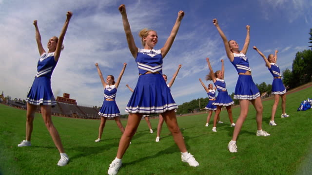 slow motion low angle wide shot pan teen female cheerleaders in uniform performing cheering routines on football field - cheerleader stock videos & royalty-free footage