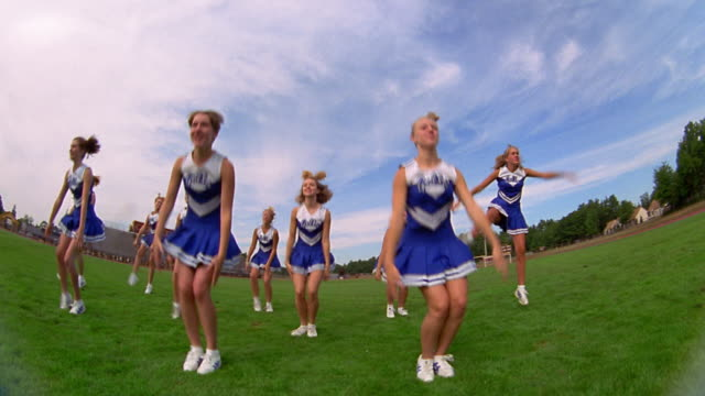 slow motion low angle wide shot pan teen female cheerleaders in uniform performing cheering routines on field - cheerleader stock videos & royalty-free footage