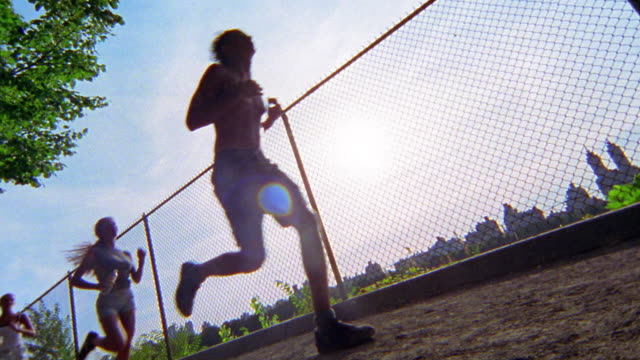 slow motion low angle wide shot pan two men and two woman jogging on running track / central park, nyc - 4人点の映像素材/bロール
