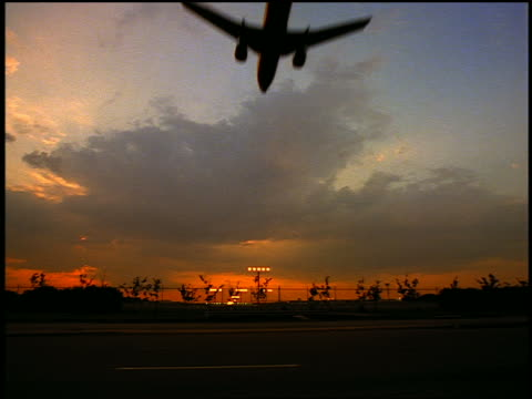 slow motion low angle wide shot silhouette of airliner descending toward runway at sunset / traffic on road in foreground - establishing shot stock videos & royalty-free footage