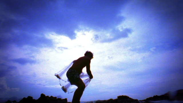 blue slow motion low angle wide shot silhouette of man throwing net into ocean / net lands on camera splashing / hawaii - hawaiianische kultur stock-videos und b-roll-filmmaterial