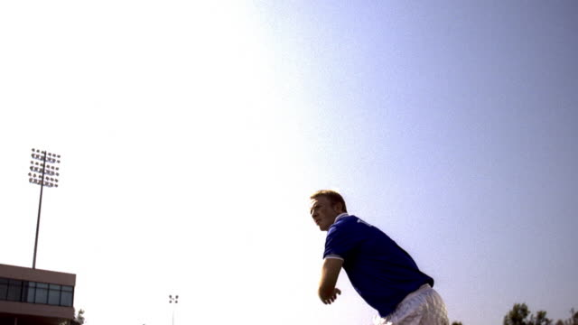 slow motion low angle wide shot soccer player in blue uniform jumping + kicking ball back over his head - whatif点の映像素材/bロール