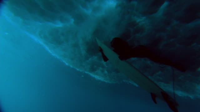 Slow motion low angle wide shot woman hanging onto surfboard as wave envelopes her / Tahiti