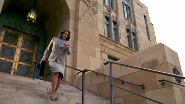stockvideo's en b-roll-footage met slow motion low angle wide shot woman in suit rushing down stairs / briefcase opening / papers flying out - attaché
