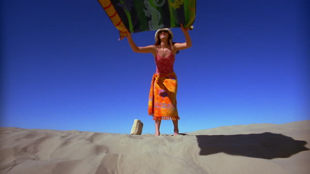 vídeos de stock e filmes b-roll de slow motion low angle wide shot woman laying beach towel on sand - toalha