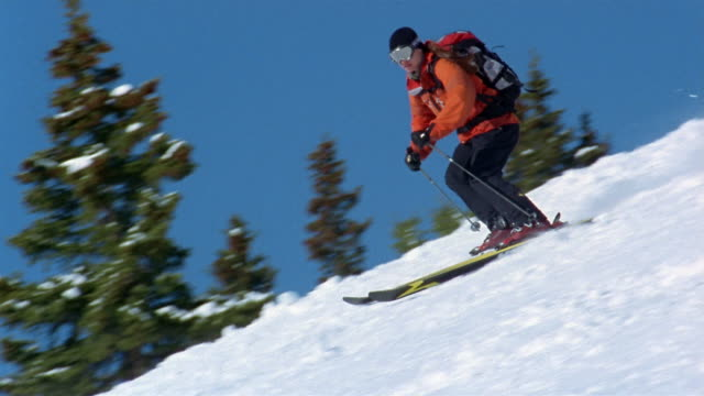 slow motion low angle wide shot woman skiing down slope with view of hills / breckenridge, colorado - ski jacket stock videos & royalty-free footage