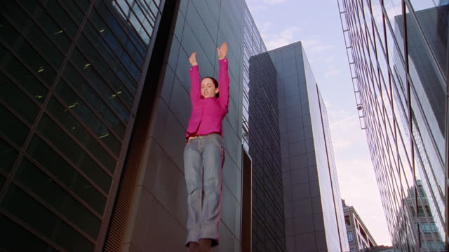slow motion low angle woman bouncing in air with buildings in background / flipping air - jumping stock videos & royalty-free footage