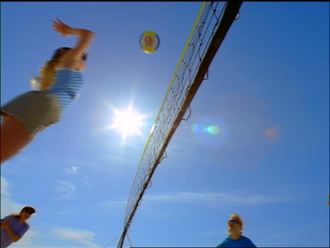 slow motion low angle woman hitting volleyball over net past player on other team outdoors - volleyball net stock videos & royalty-free footage