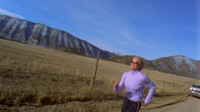 vídeos y material grabado en eventos de stock de slow motion low angle woman running on country road w/mountains and fields in background / newcastle, colorado, usa - lycra