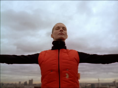 slow motion low angle woman with shaved head, arms spread out + eyes closed falling backwards / cloudy sky in background