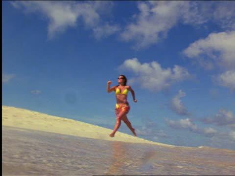 slow motion low angle woman with yellow bikini running along surf at beach / virgin islands - ワンピース型の水着点の映像素材/bロール