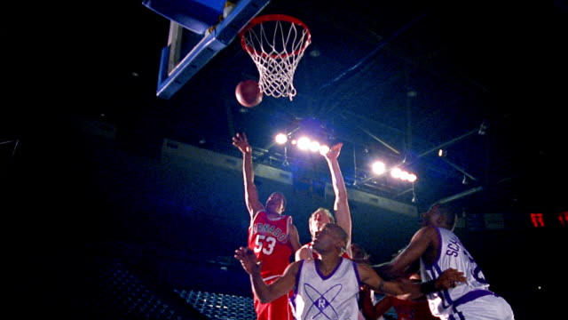 slow motion ms low angle zoom out two men's basketball teams in uniforms jumping for rebound of missed shot in arena - basket stock videos & royalty-free footage