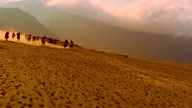 slow motion low canted aerial over crowd of people riding horses running across bromo crater / java - bromo crater stock videos & royalty-free footage