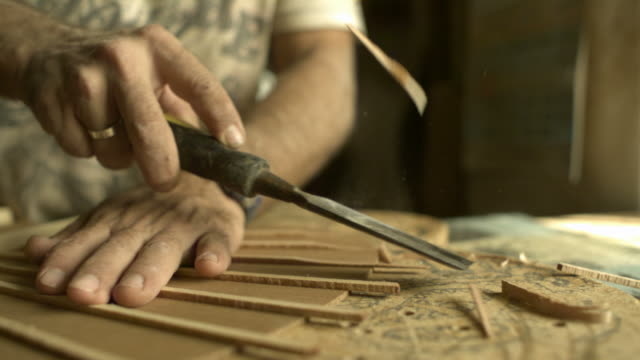 vídeos y material grabado en eventos de stock de slow motion luthier chiselling excess wood from guitar shell, spain (individual frames may also be used as a still image. each frame in its raw state is about 6mb or about 12mb as a 16 bit tiff) - craft