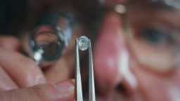 Slow motion macro close up of experienced goldsmith controlling a quality of diamond stone, selected for making jewels in workshop.