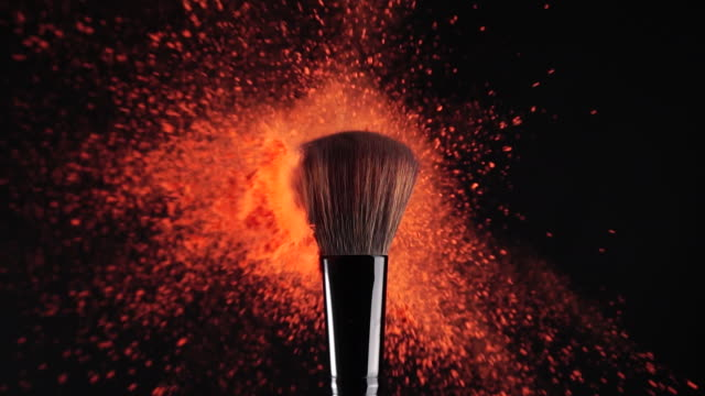 slow motion: makeup brush and red powder exploding - make up stock videos & royalty-free footage