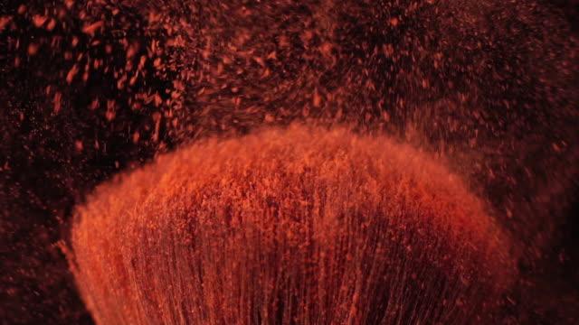 vidéos et rushes de slow motion: pinceau de maquillage poudre de propagation sur fond noir - pinceau à blush